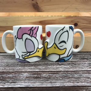 [Front View] Pair of white mugs, one with Daisy Duck, and the other with Donald Duck. They are facing eachother and when you put the mugs together it looks like they're kissing. Both characters are in full color with a red heart next to their face. Both characters are on each mug with just the view of their head.