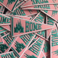 A batch of patches strewn, all of them are triangular like a banner and say HOME next to a castle in teal on top of a pink color.