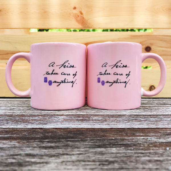 "[Back View] Both mugs have written in the center, ""a kiss takes care of anything."" in script, with a small dark purple silhouette of two paper lanterns from the Rapunzel movie."