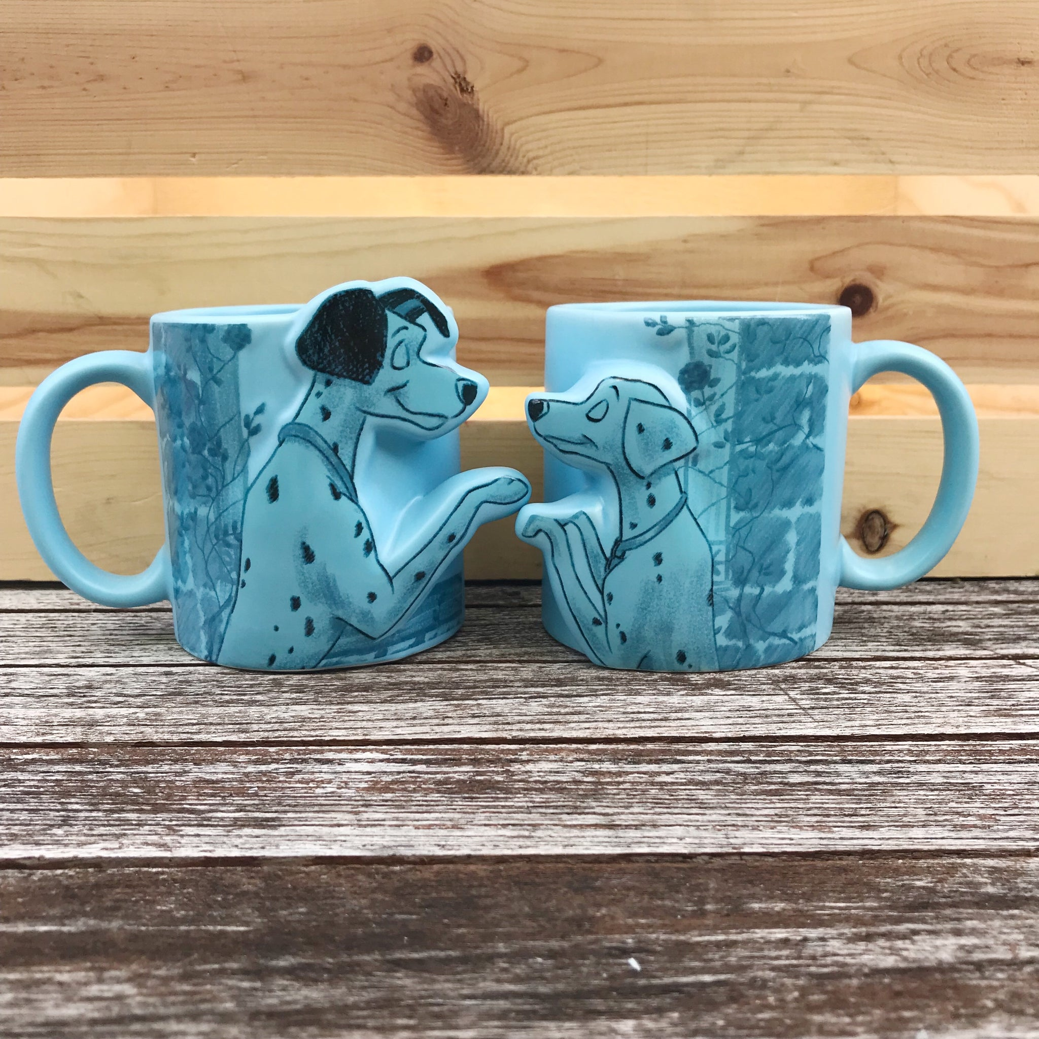 [Front View] Pair of pastel blue mugs with curved handle, 1 Mug has male Dalmation, and the other, a female Dalmation facing eachother.  Both drawn in a black outline with watercolor background of flowers and a brick wall in darker shade of blue.