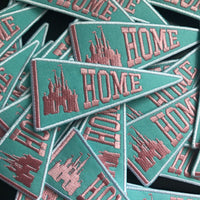 A batch of patches strewn, all of them are triangular like a banner and say HOME next to a castle in pink on top of a mint color.