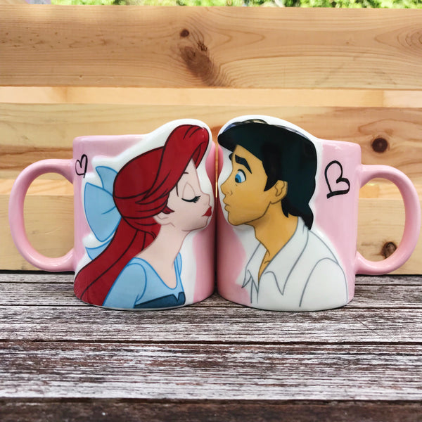 [Front View] Pair of pastel pink mugs with curved handle in the same color. Mugs have Ariel and Eric facing eachother leaning in for a kiss. Both characters are in full color, with a white outline around them and they are both 3D and pop outwards slightly. Both cups have a small black heart outline behind the head of each character.