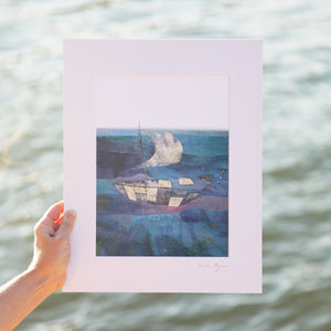 Framed Print of an illustration by Irish Visual Artist Deirdre Byrne. A boat made of gold and black and white cut outs sails over a mixed media blue posca sea. Photo is taken outside with river in the background