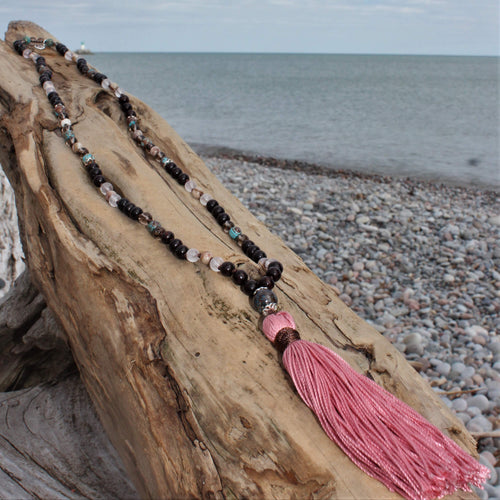 Always Surrounded Crystal Mala wil pink tassle on beach