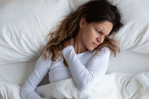 Young woman suffering from neck pain caused by using an old pillow