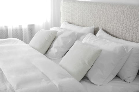 pillows and a comforter laid out on a bed