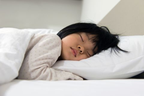 Young child sleeping safely and comfortably using a pillow.