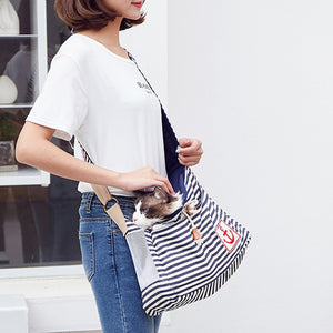 left side of Qbleev striped dog sling blue and white for puppy and cats carried by  a girl