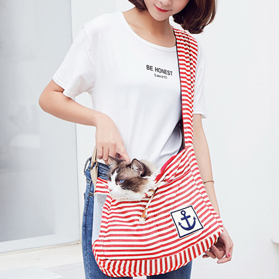 front of Qbleev striped dog sling red and white for puppy and cats carried by a girl