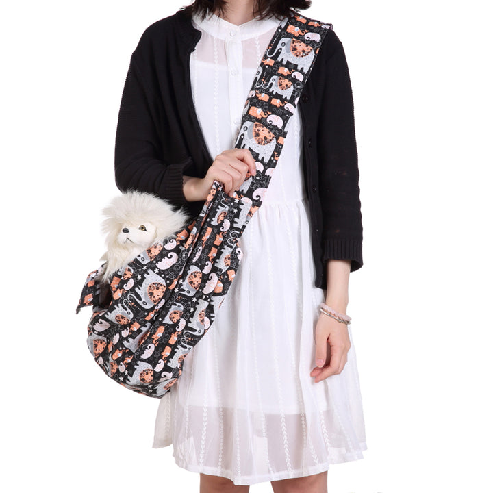 Qbleev orange printed dog sling for puppy & cats with puppy inside carried by  a girl