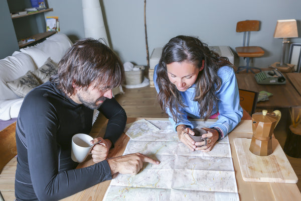 Couple drinking coffee around a wooden table where they study a hiking map.