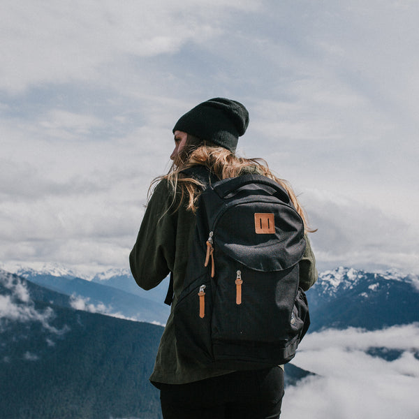 Women hiking with the rift backpack in the mountains wearing all black and facing away from the camera.