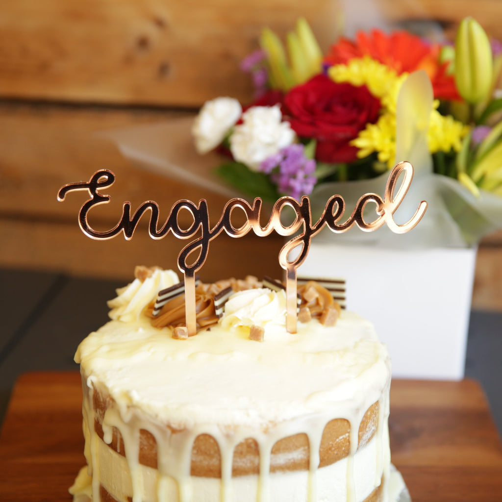 The beautiful cake topper can be in acrylic or bamboo ply. It features the word Engaged in beautiful script text.