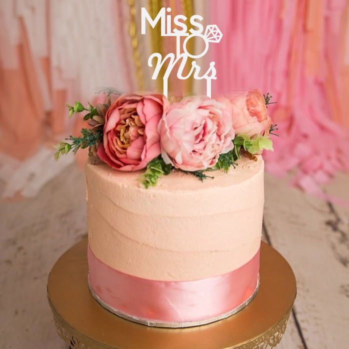 The beautiful cake topper can be in acrylic or bamboo ply. It features the words Miss to Mrs  in beautiful script text with a beautiful diamond ring as to O.