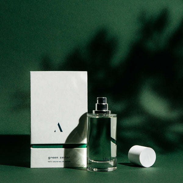 Abel Perfume Green Cedar lifestyle image in front of green background with shadows