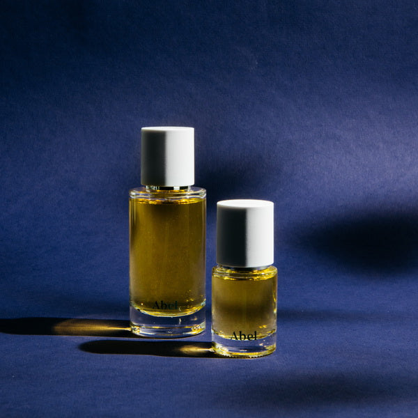 Abel Cobalt Amber Perfume regular and small size in front of blue background