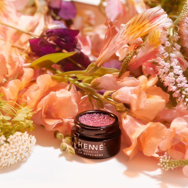 Henné Organics Lip Exfoliator Rose Diamonds in front of bunch of flowers
