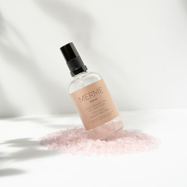 Merme Berlin Facial Antioxidant Mist With Rose Quartz 100% Organic Rosewater standing on rose quartz pepples