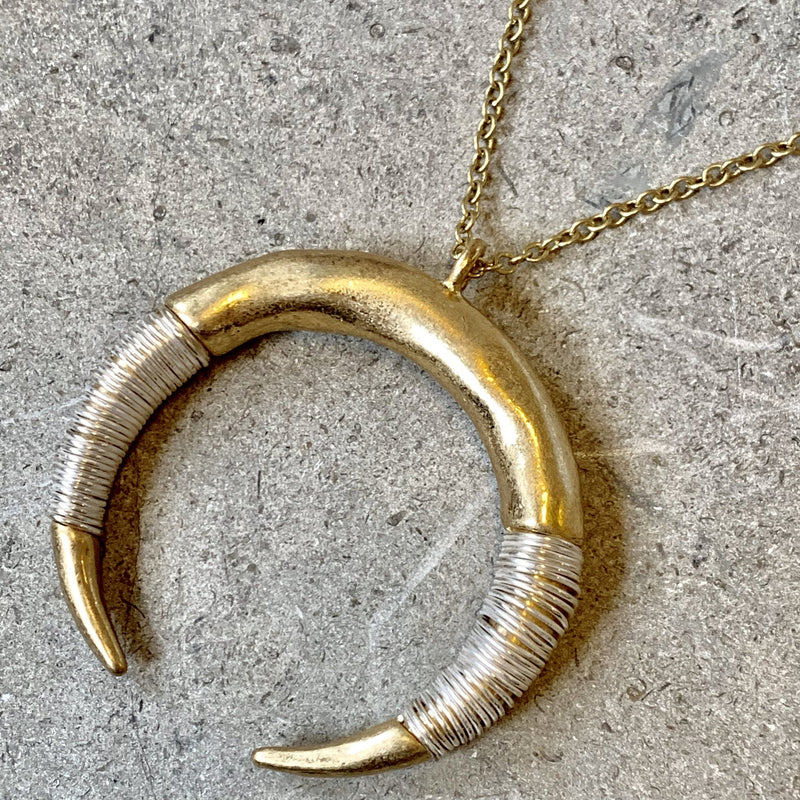 Gold crescent pendant with silver wire detailing.