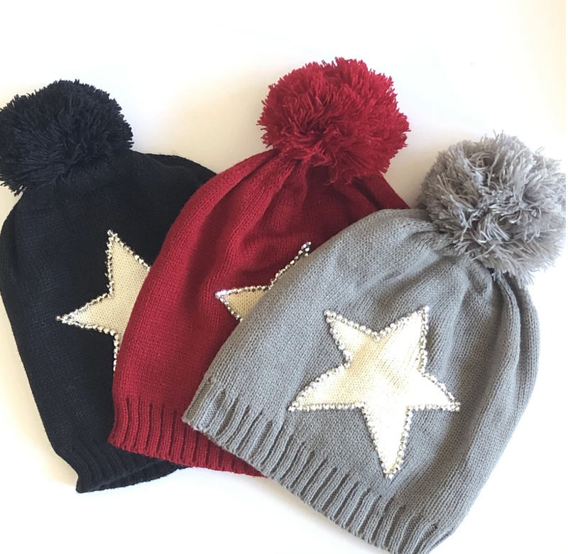 Three winter hats with pom poms and star detailing