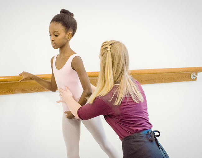 Teacher works with a student during a ballet lesson.