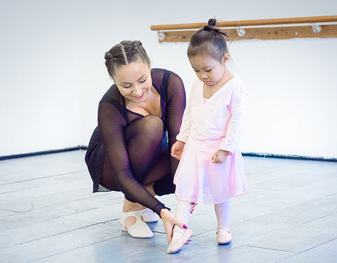 A teacher shows a young girl ballet positions in a private lesson in London.