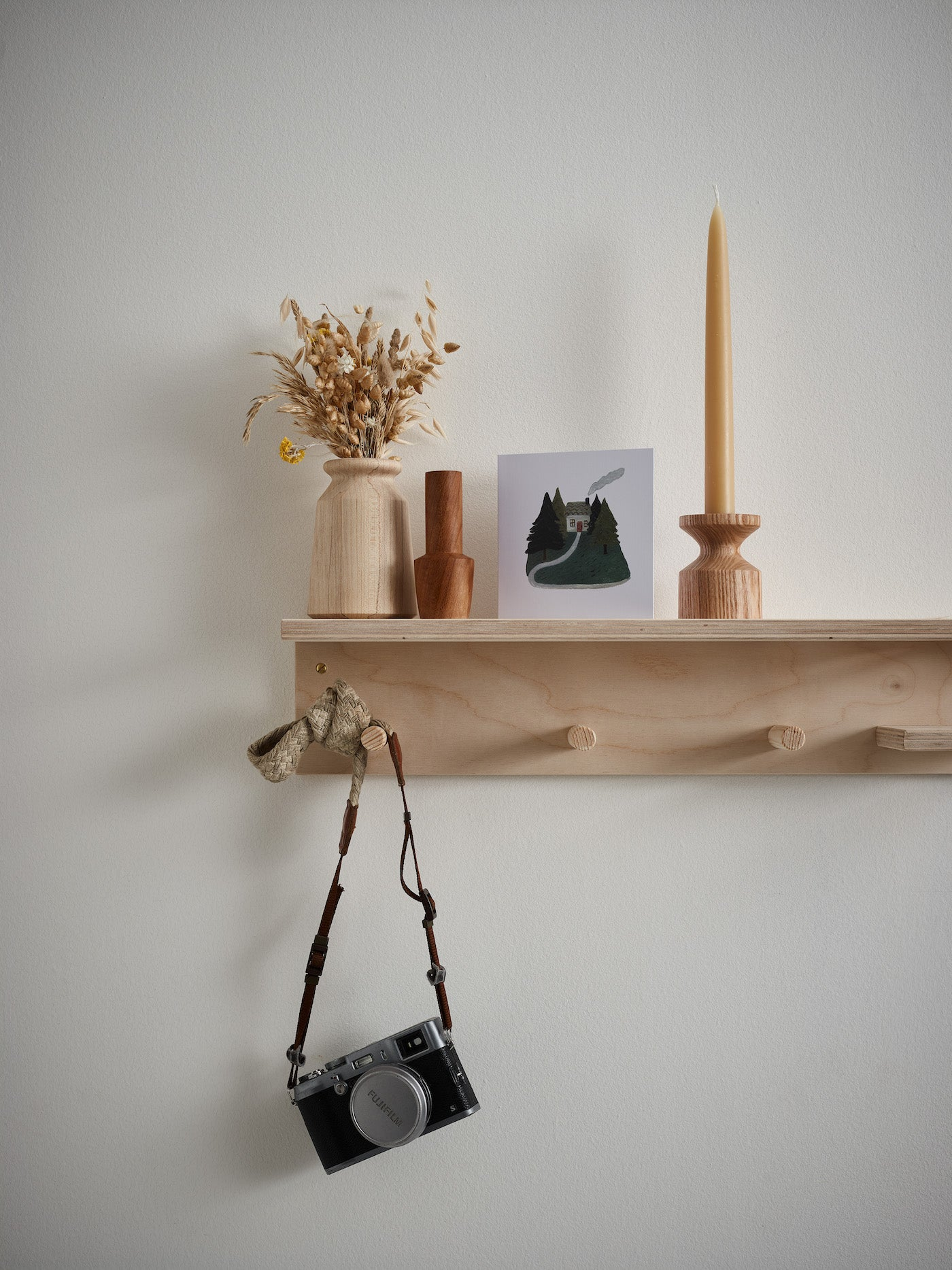 a wooden shelf with candle, housewarming card and camera