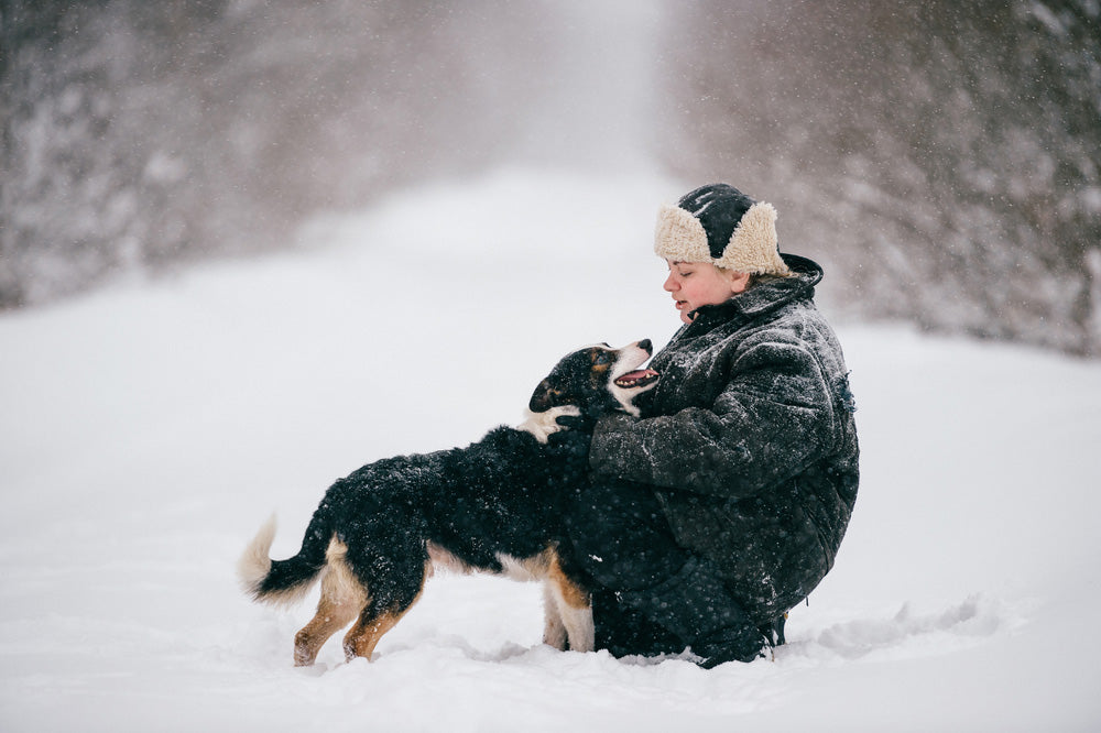 Woman and dog out playing in the falling snow