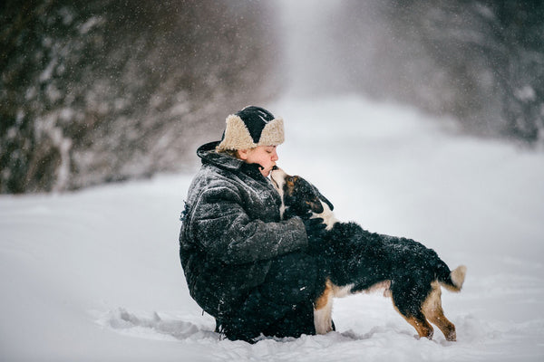 Woman showing dog affection in falling snow