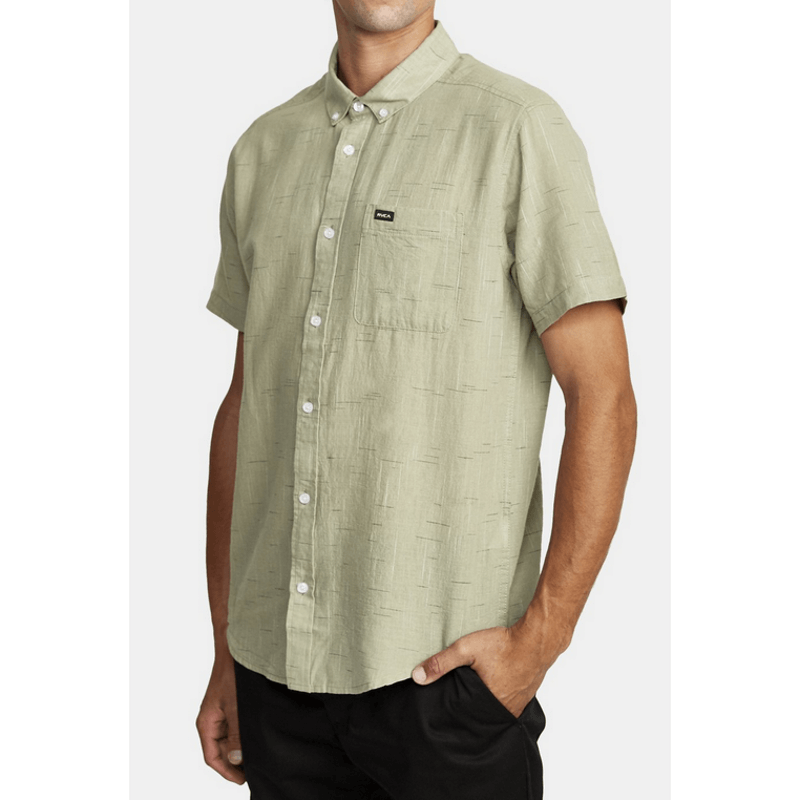 sage green shirt with pocket on left chest with logo badge