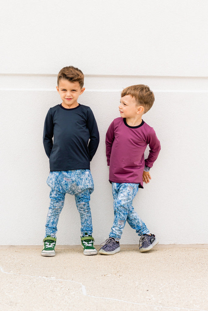 Two young boys in hand made clothes.  Hi Lo Long sleeve tees in Ruby and Onyx, with denim pants.