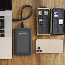 Load image into Gallery viewer, OYEN DIGITAL U32 Shadow Dura | Rugged Portable SSD [USB-C] plugged into macbook pro with phone.
