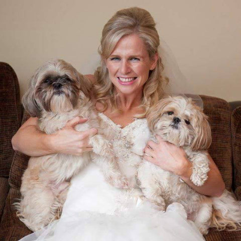 a bride holding two dogs