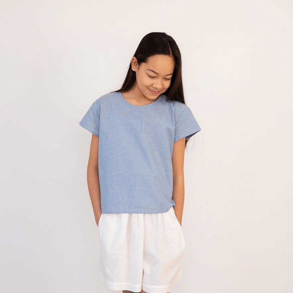 Teen girl wearing blue cropped box t-shirt and white shorts