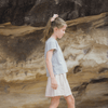 Teenage girl wearing grey top and white shorts, walking along rocks