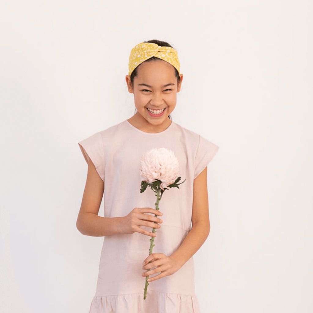 Tween girl wearing a pink summer dress and holding a peony