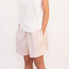 Tween girl with hands in pockets wearing white cotton t-shirt and pink shorts