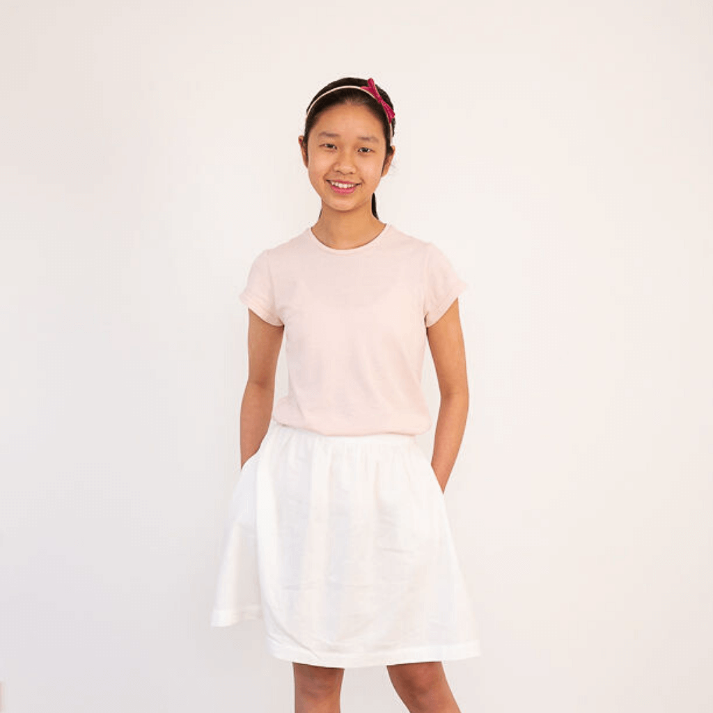 Teen girl wearing pink cotton t-shirt and white skirt