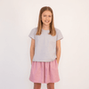 Tween girl wearing plain grey cotton t-shirt and pink shorts