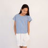 Tween girl wearing blue cotton top and white shorts