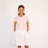 Teenage girl wearing pink cotton t-shirt and white skirt with hands in pockets