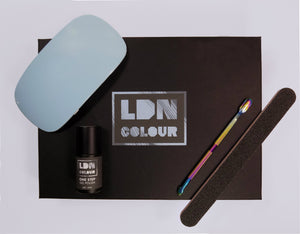 An overhead shot of the best gel nail kit created by LDN Colour. It contains a gel nail polish that sets in one step, a LED gel nail dryer, a cuticle pusher and a nail file.