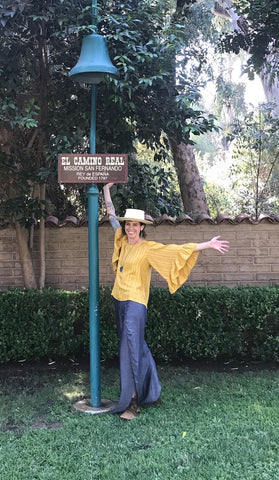 Amanda Gries standing next to an El Camino Real bell at the San Fernando Mission