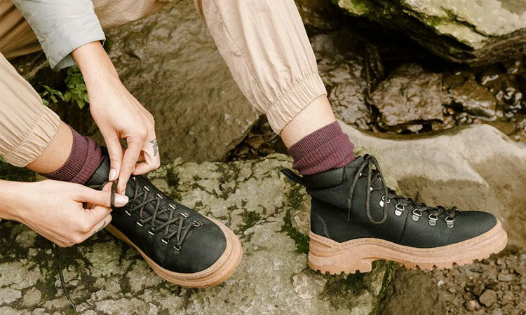 Person wearing black vegan lace-up hiking boots