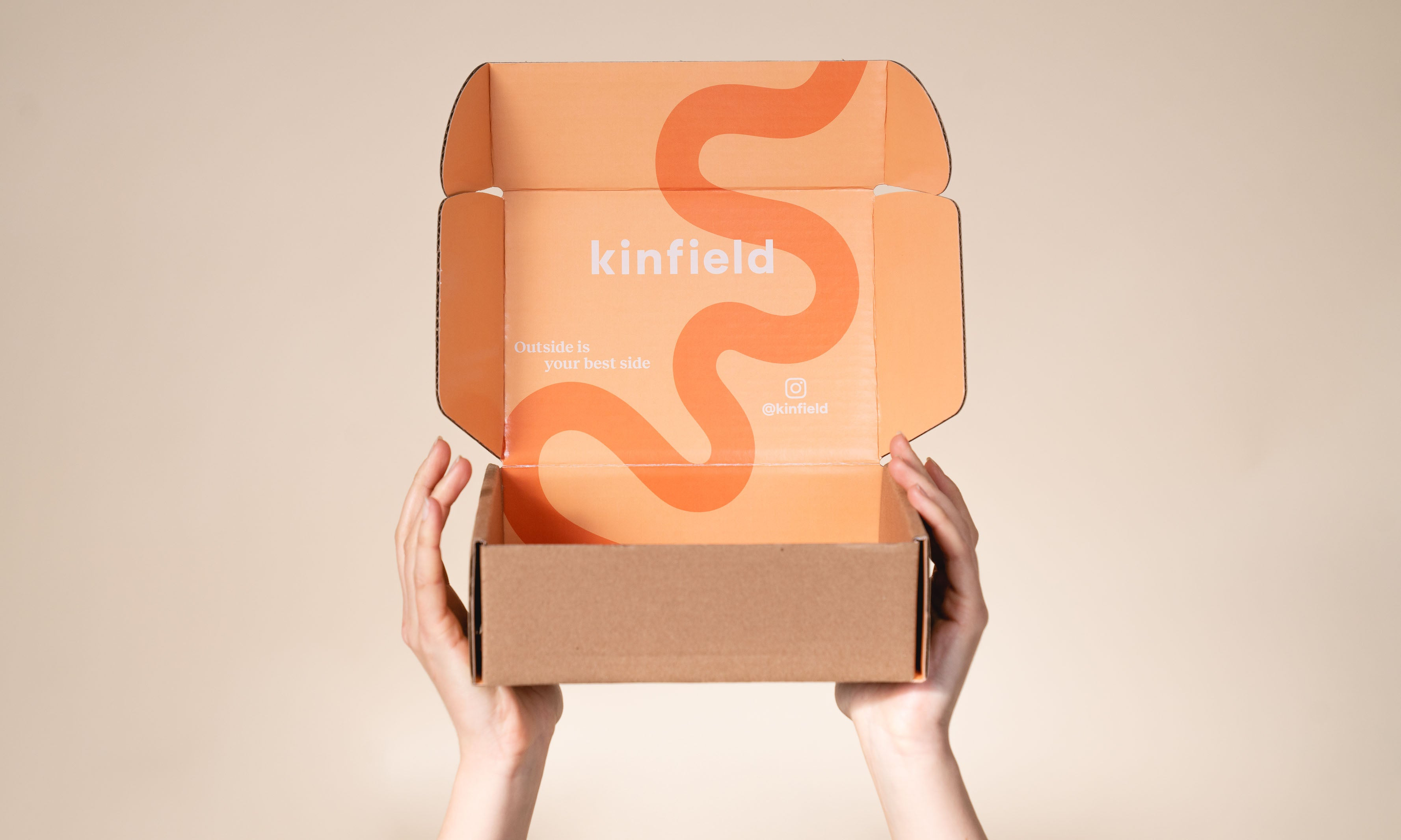 Hand holding open shipping box with Kinfield orange branding