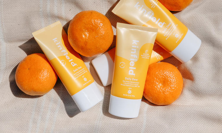 Tubes of Kinfield's Daily Dew SPF 35 lay on a beach blanket with citrus fruit