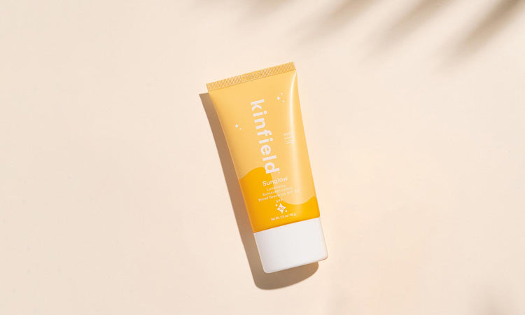Kinfield Sunglow SPF 30 rests on a beige background with the shadow of a palm tree in the corner.