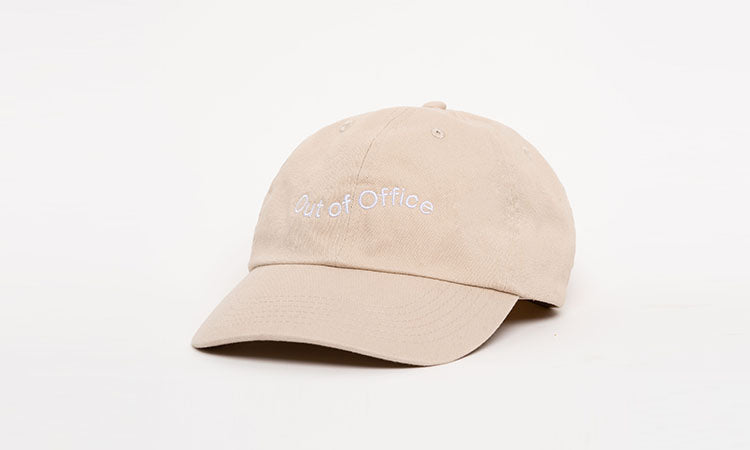 Sand-colored baseball cap that says 'Out of Office' in white