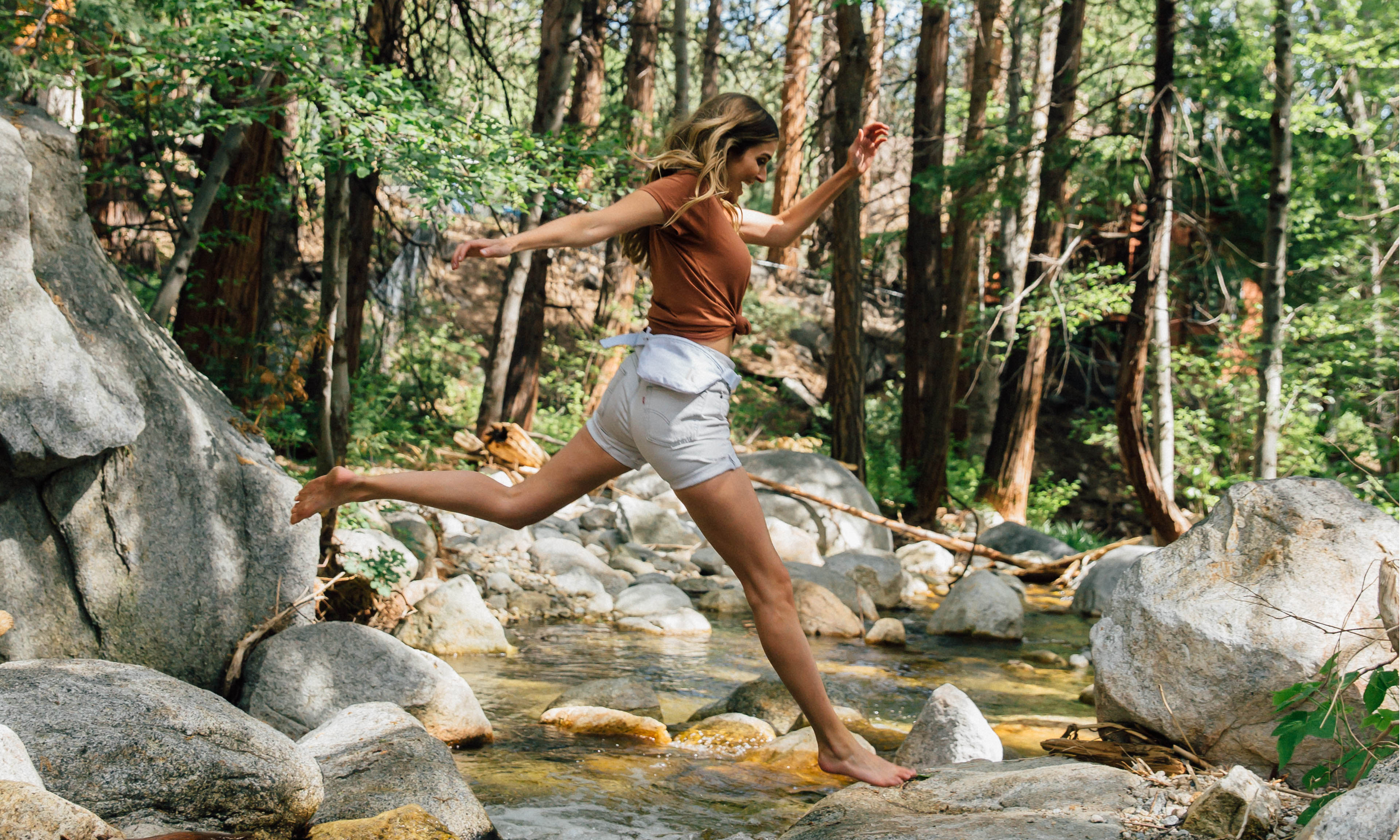 Woman energetically leaps across a small river