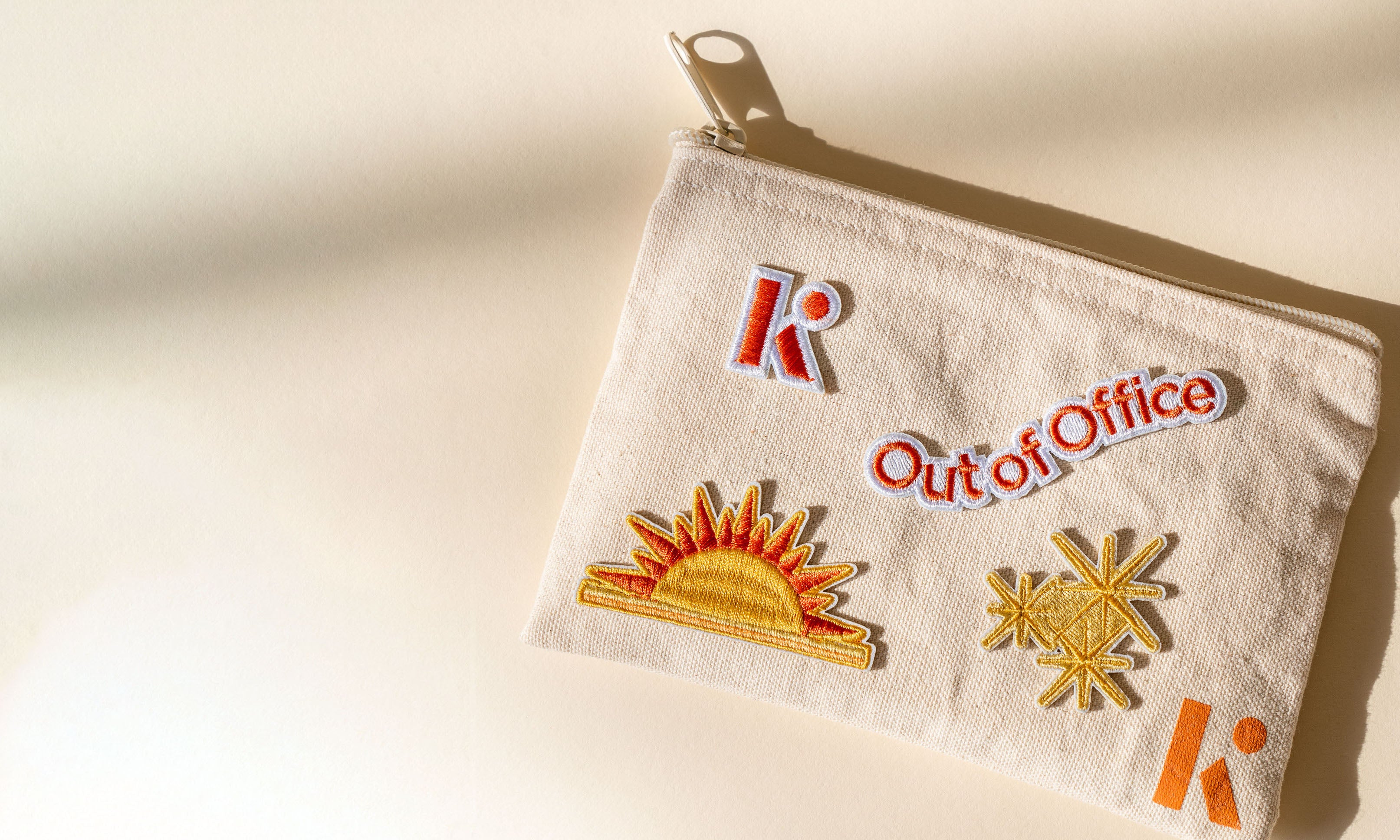 Brightly colored Kinfield patches adorn a beige-colored cotton zippered pouch.